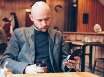 Adult bald gloomy man drinking coffee from paper cup and using mobile phone at cafe. The Adult bald gloomy man drinking coffee from paper cup and using mobile royalty free stock photos