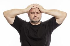 Adult bald man holds his head in his hands royalty free stock photo