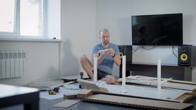 Adult bald man wearing home clothes is assembling furniture in the apartment. He is looking for table parts in a pack stock video