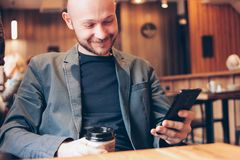 Adult bald smiling man drinking coffee from paper cup and using mobile phone at cafe. The Adult bald smiling man drinking coffee from paper cup and using mobile royalty free stock photos