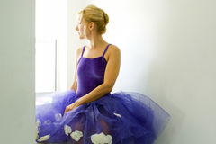 Adult ballerina. Wearing purple tutu is turned in profile and looking out window Royalty Free Stock Photo
