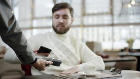Adult man paying the cafe bill with his smartphone while sitting by table with his girlfriend. Adult bearded man paying the cafe bill with his smartphone while stock video footage
