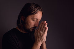 Adult bearded man praying in dark room Stock Photo