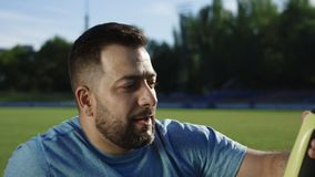Man drinking water on stadium. Adult bearded man in sportswear drinking water from training bottle sitting on green stadium after workout stock footage