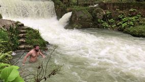 An adult man bathes at the foot of a waterfall in refreshing water. An adult and a bearded man washes his face in refreshing water, behind him is a waterfall stock video