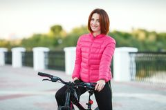 Adult beautiful redhead woman with bob haircut posing on bicycle in autumn city river pier Royalty Free Stock Images