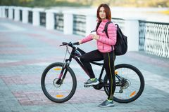 Adult beautiful redhead woman with bob haircut thinking drinking morning coffee posing on bicycle in autumn city river pier stock photography