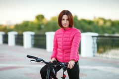 Adult beautiful redhead woman with bob haircut posing on bicycle in autumn city river pier Stock Photo