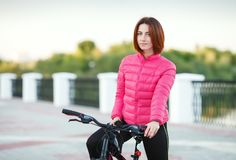 Adult beautiful redhead woman with bob haircut posing on bicycle in autumn city river pier Royalty Free Stock Photography