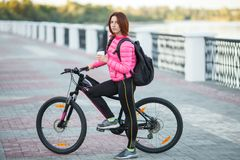 Adult beautiful redhead woman with bob haircut thinking drinking morning coffee posing on bicycle in autumn city river pier Royalty Free Stock Image
