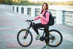 Adult beautiful redhead woman with bob haircut thinking drinking morning coffee posing on bicycle in autumn city river pier Royalty Free Stock Photography