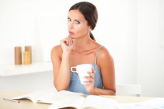 Adult beautiful woman wondering while studying Royalty Free Stock Images