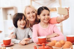 Adult beautiful woman makes selfie on smartphone with her grandchildren who drink tea at kitchen. Adult beautiful women makes selfie on smartphone with her Royalty Free Stock Photos