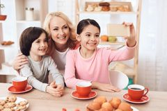 Adult beautiful woman makes selfie on smartphone with her grandchildren who drink tea at kitchen. Adult beautiful women makes selfie on smartphone with her Stock Image