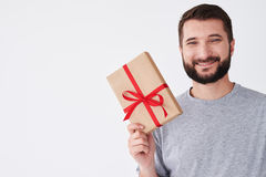 Adult berded man smiling with present, looking on his right text Stock Photo