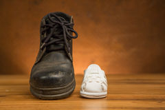 Adult black shoes and kid white shoes Royalty Free Stock Images