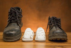 Adult black shoes and kid white shoes Royalty Free Stock Image