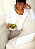 Adult black woman eating healthy green salad. Top view portrait of an adult black woman eating healthy green salad while is sitting on sofa in front of her Stock Photos
