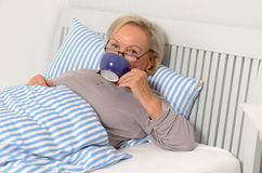 Adult Blond Woman on her Bed Holding her Cup Stock Photography