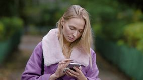 Adult blonde businesswoman is standing alone in park and typing message on her smartphone in daytime stock video