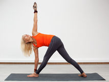 Adult blonde woman doing turning triangle pose Royalty Free Stock Photography