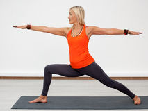 Adult blonde woman doing warrior pose Stock Photos