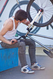 Adult boy repair his silver bike Stock Photos