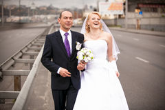 Adult bride and groom hugging on empty road Stock Photography