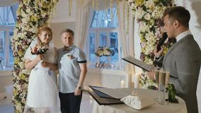 Happy adult couple getting married at wedding hall. Adult bride wearing wedding dress with her groom stands under the flower arch in wedding hall. The party host stock video