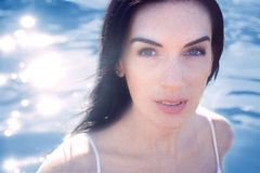 Adult brunette woman on a backaground of blue water, close up , outdoor Royalty Free Stock Photos