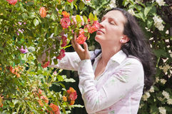 Adult brunette woman in garden with roses Royalty Free Stock Images