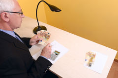 Adult business man working with calculator and banknotes Stock Photography