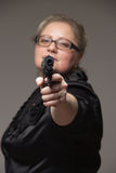 Adult business woman with black gun on a gray background Royalty Free Stock Image