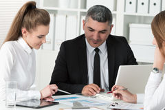 Adult businessman consulting his young female colleague. During business meeting. Partners discussing documents and ideas Stock Photos