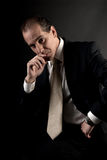 Adult businessman serious thinking dark background stock photo