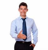 Adult businessman standing with greeting gesture. A portrait of an adult businessman on blue shirt standing with greeting gesture while looking at you on Stock Image