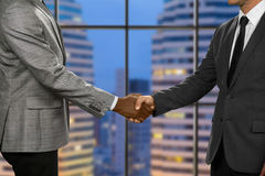 Adult businessmen shake hands. Greeting of men in megalopolis. Pacified by rules of etiquette. Topmanagers at the meeting Stock Image