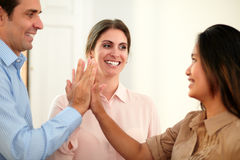 Adult businesswoman huddle her hands with coworker Stock Images