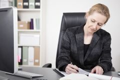 Adult Businesswoman Writing on Top of her Desk Royalty Free Stock Photography