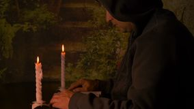 Adult caicasian monk sitting at table at night, Man read book at night with candles light. Monk reading book slide. Fingers. Man with hood on head sitting and stock video footage