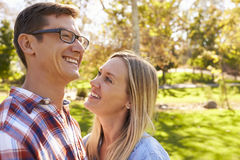 Adult Caucasian couple embracing in a park looking away Royalty Free Stock Photo