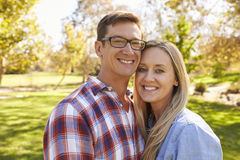 Adult Caucasian couple embracing in a park looking to camera Royalty Free Stock Photos