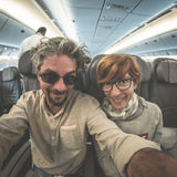 Adult caucasian couple taking selfie inside plane. Fish eye view from below. Concept of people traveling, natural light. Royalty Free Stock Images