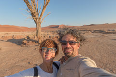 Adult caucasian couple taking selfie at Sossusvlei in the Namib desert, Namib Naukluft National Park, main travel destination in N. Amibia, Africa Stock Photography