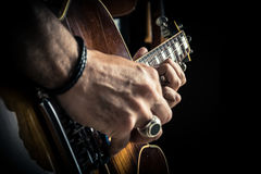 Adult caucasian guitarist portrait playing electric guitar on grunge background. Close up instrument detail. Music Royalty Free Stock Images