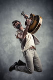 Adult caucasian guitarist portrait playing electric guitar and jumping on grunge background. Music singer modern concept.  royalty free stock images