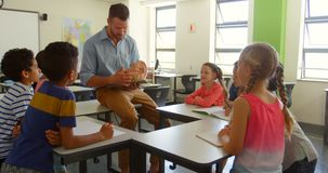 Adult Caucasian male teacher explaining anatomical model in classroom at school 4k. Front view of adult Caucasian male teacher explaining anatomical model in stock video footage