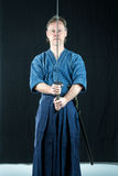 Adult caucasian male training Iaido holding a Japanese sword with focused look. Royalty Free Stock Photography