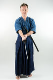Adult caucasian male training Iaido holding a Japanese sword with focused look. Stock Images
