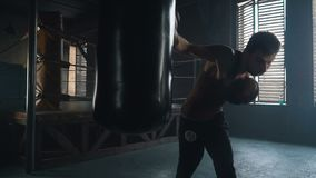 Adult caucasian man boxing and punching bag in vintage gym slowmo. Adult caucasian man wearing gloves boxing and punching bag in vintage gym with windows on stock footage